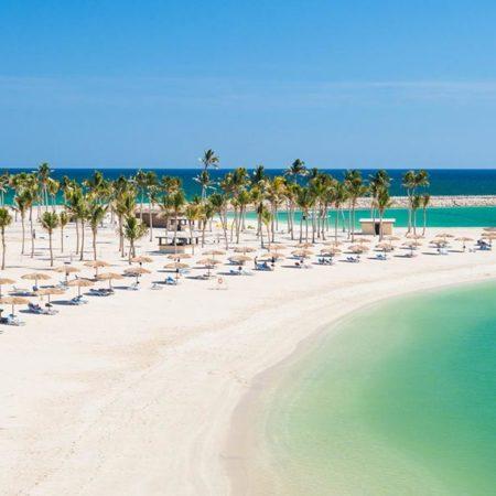Plage de sable blanc d'Oman avec alignement de parasols au pied des palmiers