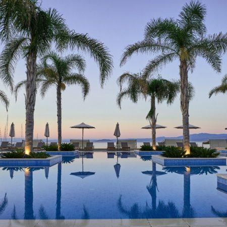 Piscine extérieure avec palmiers parsemés dans hotel Miraggio Thermal & Spa Resort à Chalkidique